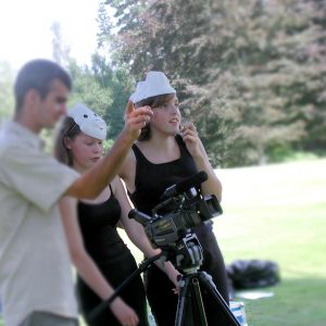 Two young girls are wearing masks on their head and using a movie camera. A person on the left hand side gives them direction.
