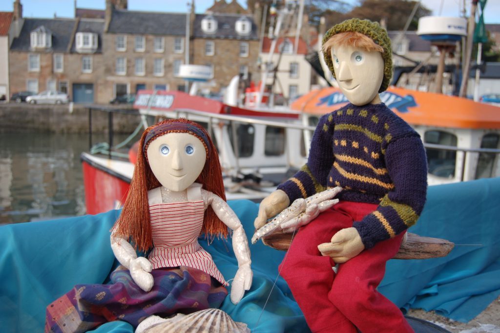 Two puppets sit in front of a harbour, wearing marine clothes