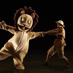 a performer in a Lion is pulled by its arm by another performer.