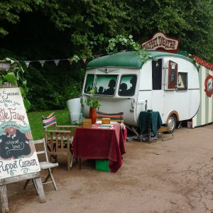 a caravan puppet theatre is parked on the background. There is a table with chair and a Puppet Caravan sign in front of it.