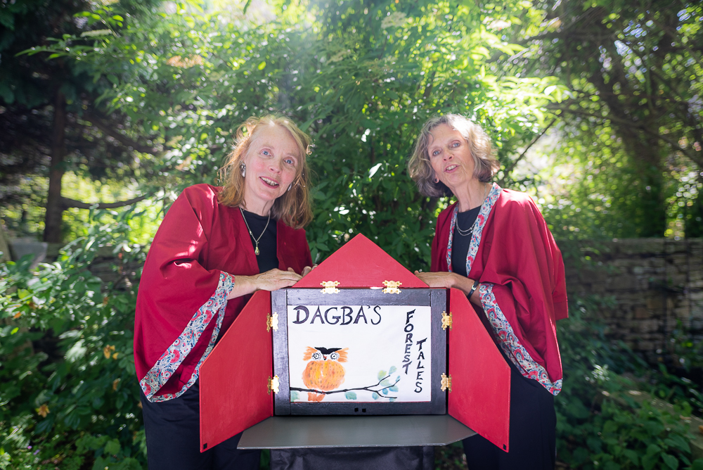 Two performers stand before a tree and behind a open box with a white board at its centre. On the board is drawn an owl by the performance's title.