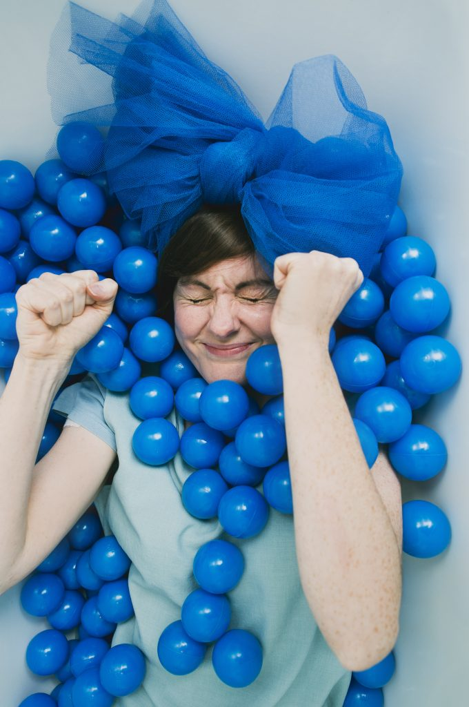 A perfomer is lying down with eyes closed and fist clenched, arms up. There are blue playing balls around them and a blue bow on their head.