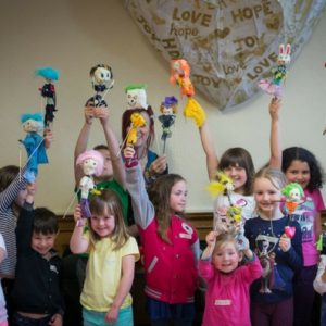Children stand in a group holding hand made puppets above their heads.