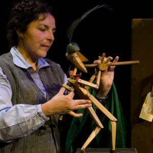 A puppeteer on the left is handling a wooden puppet playing the flute. An old leather suitcase is visible on the right of the image.