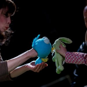 a puppeteer on the left is holding a blue bird puppet, touching a green rabbit soft toy held by a child on the right.