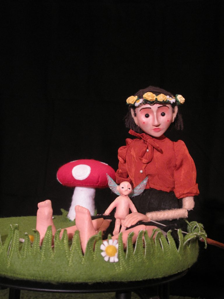 a puppet wearing a flower crown is sat on artificial grass and looks out to the viewer. There is a small fairy puppet on her lap and a fabric mushroom behind her.