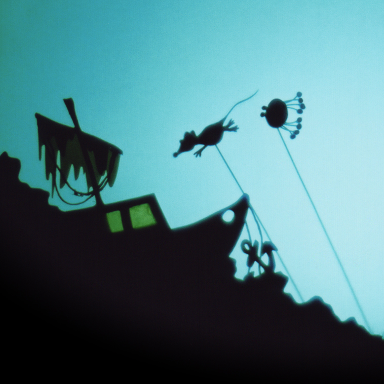 The wreckage of a boat with two shadow puppets swimming toward it.
