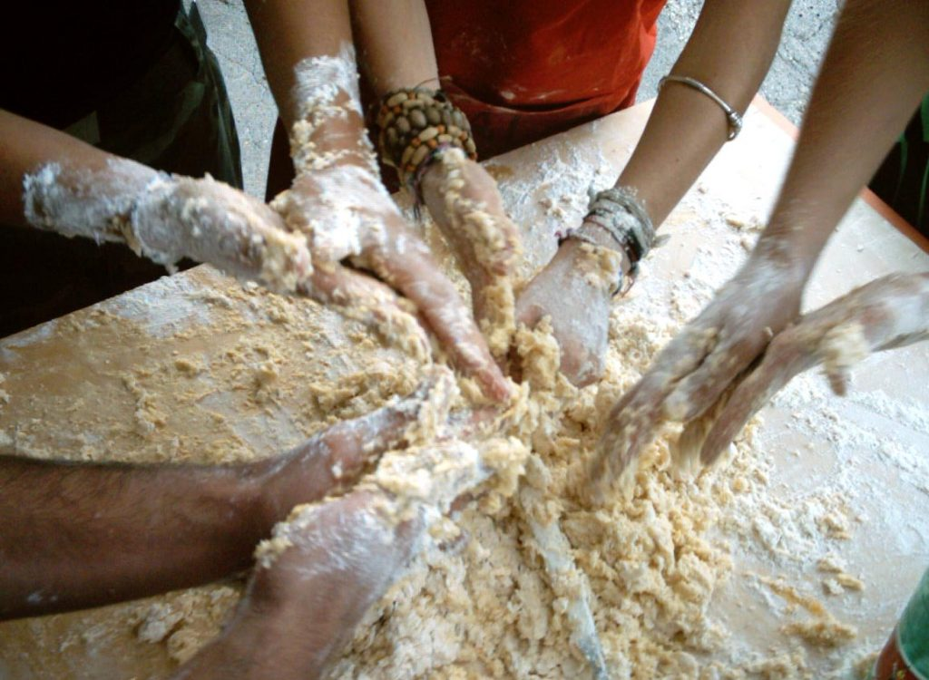 a group of hands are joined together mixing flour above a table.