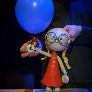 a puppet in a red dress with glasses on and ginger hair holds a balloon. The puppeteer's hands are visible behind it.